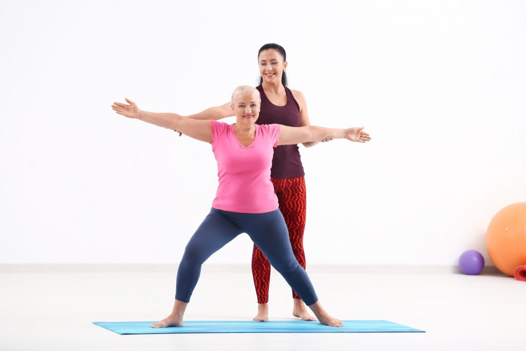 Mature woman with personal yoga instructor indoors